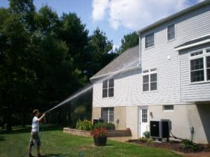 Zach of Complete Pressure Wash power washing a vinyl-sided house